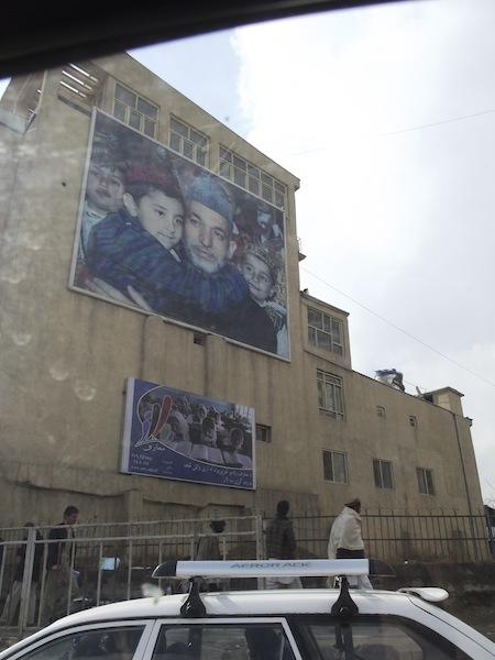 Kabul billboard - Politician hugging a child, photo of girls at school underneath.